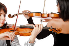 Two violinists representing the dual work of the grant writer and grant manager
