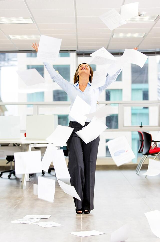 Excited businesswoman throwing papers in the air.jpeg