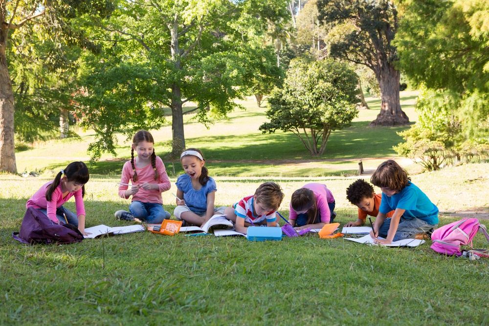 School children doing homework on grass on a sunny day.jpeg