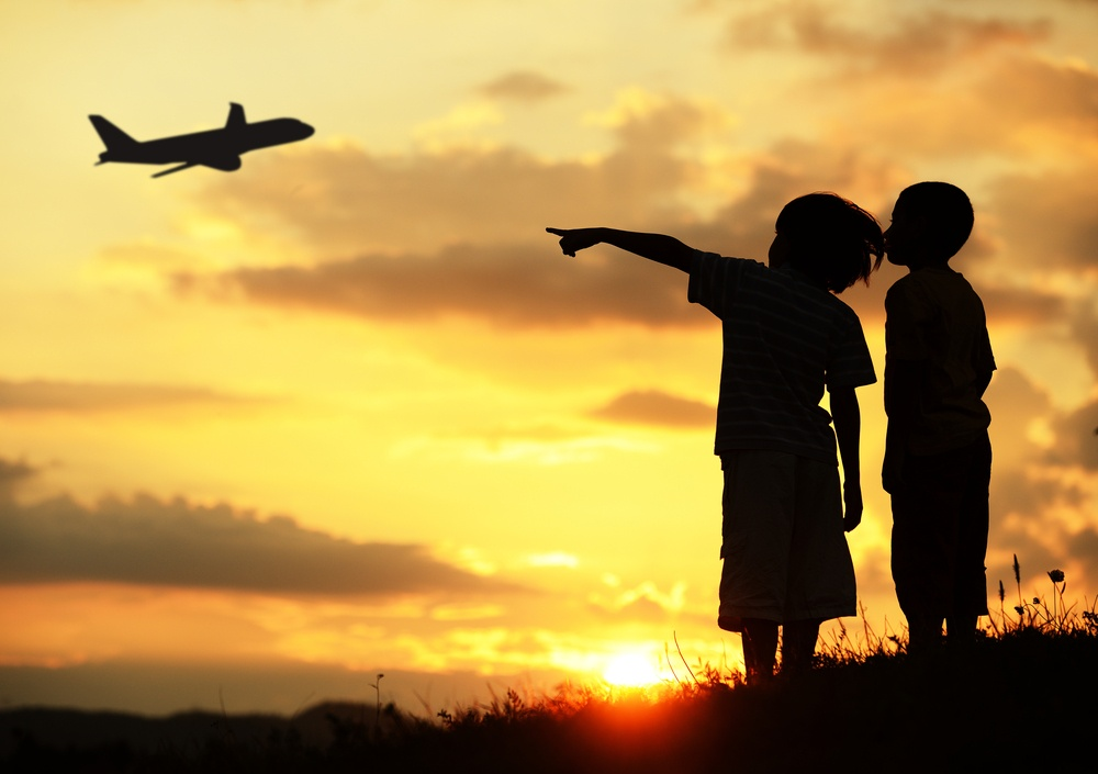 Two kids silhouette on meadow looking at airplane in air.jpeg